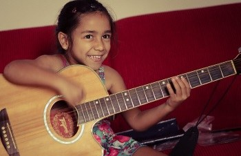 little girl holding oversized acoustic guitar