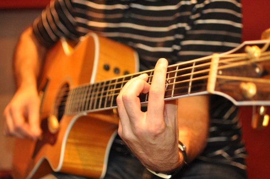 detail shot of hands pressing down strings on acoustic guitar fretboard