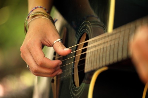 hands picking guitar strings with boho jewelry