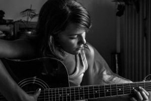 black and white image of young woman playing acoustic instrument