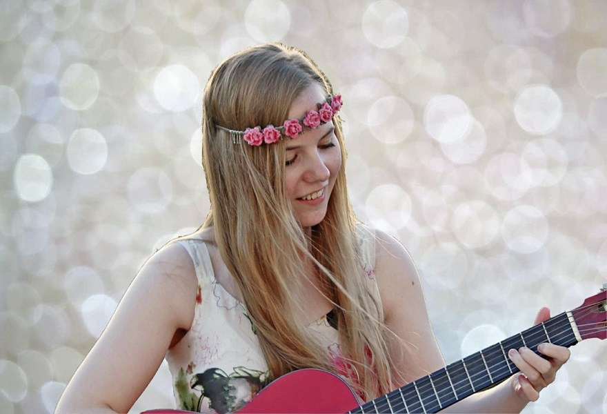 girl with flower headband playing pink guitar