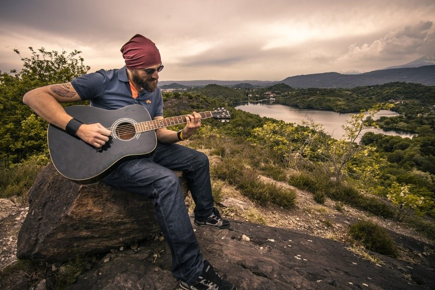 guitarist sitting on a hillside with a blue acoustic instrument