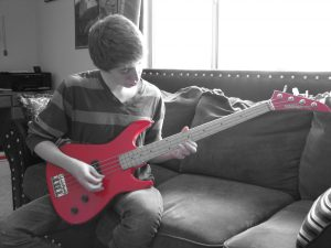 young man practicing a red guitar in his livingroom.