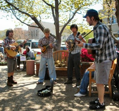group of musicians playing guitars and mandolins outdoors.