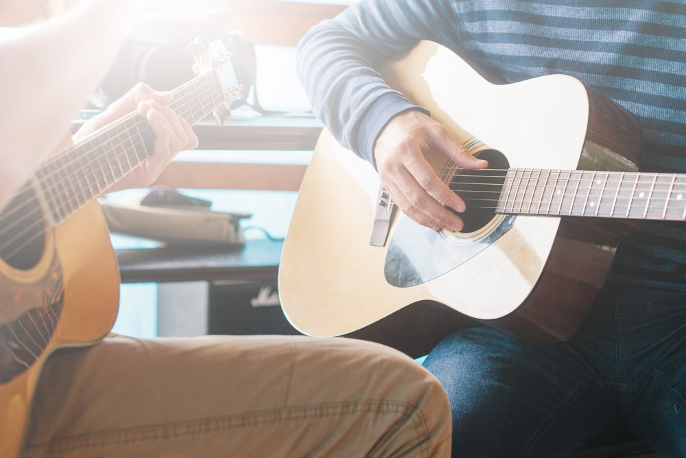 image of two people getting guitar training
