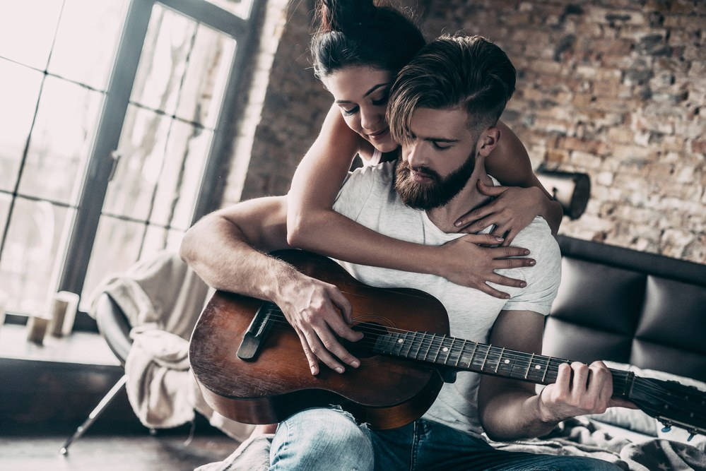 wife helping handsome beared man master the best way to learn guitar