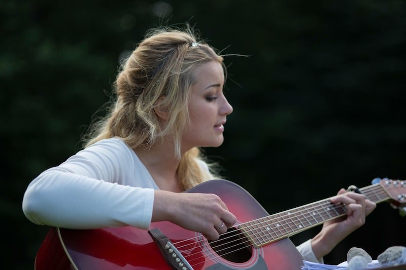 image of blonde woman with small hands playing a guitar